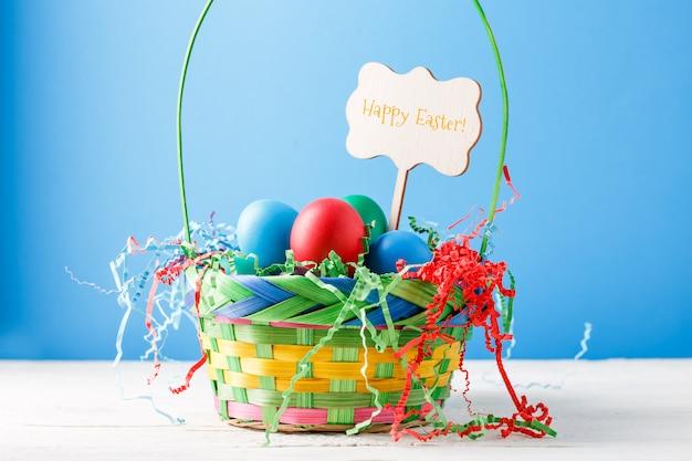 Imagem de cesta com ovos coloridos com desejo de feliz páscoa