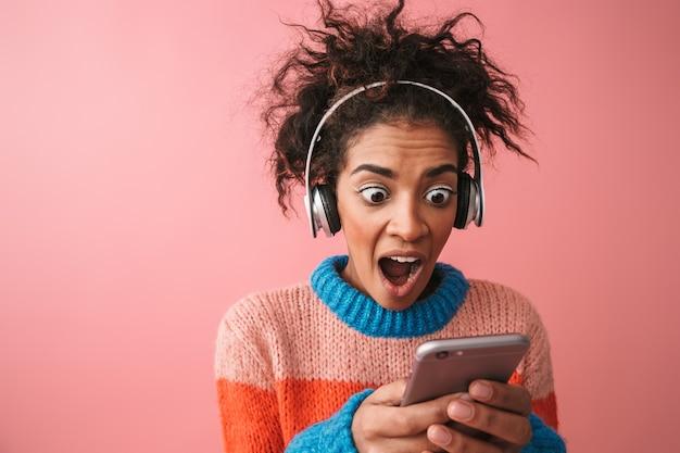 Imagem de chocado emocional bela jovem africana posando música isolada com fones de ouvido usando telefone celular.