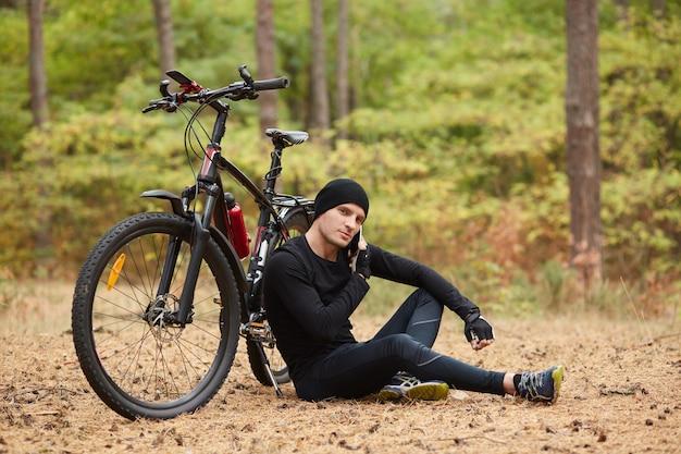 Imagem de ciclista de montanha masculina descansando em uma viagem de bicicleta, sentada no chão sob uma árvore com sua bicicleta deitada ao lado dele