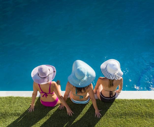 Imagem de cima de três meninas de biquíni de costas voltadas para o meio-fio de uma piscina com chapéus combinando com o biquíni próximo à grama