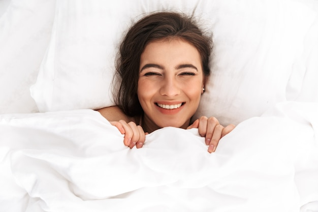Imagem de cima de uma mulher pacífica de 20 anos com cabelo escuro rindo, deitada na cama sob um lençol branco