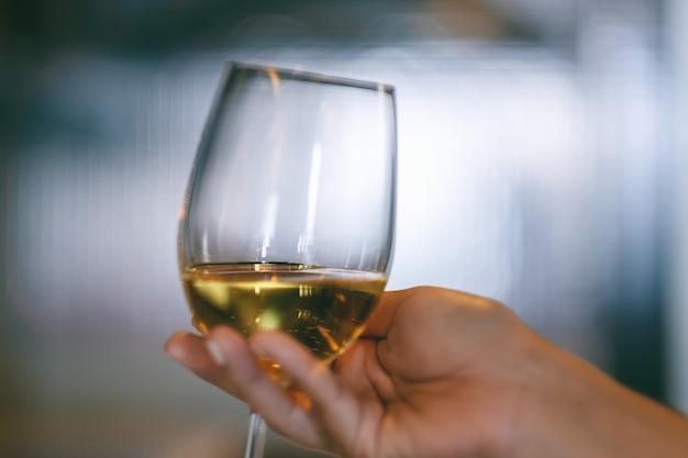 Imagem de close da mão de uma mulher segurando uma taça de vinho com fundo desfocado