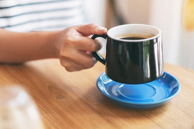 Imagem de close da mão de uma mulher segurando uma xícara preta de café quente na mesa de madeira