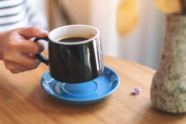 Imagem de close da mão de uma mulher segurando uma xícara verde de café quente na mesa de madeira
