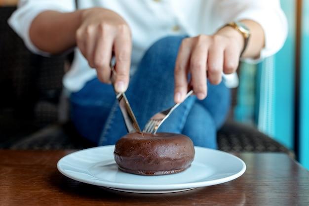 Imagem de close das mãos de uma mulher cortando um pedaço de donut de chocolate com uma faca e um garfo no café da manhã na mesa de madeira