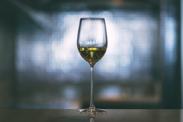 Imagem de close de champanhe em uma taça de vinho com fundo claro desfocado