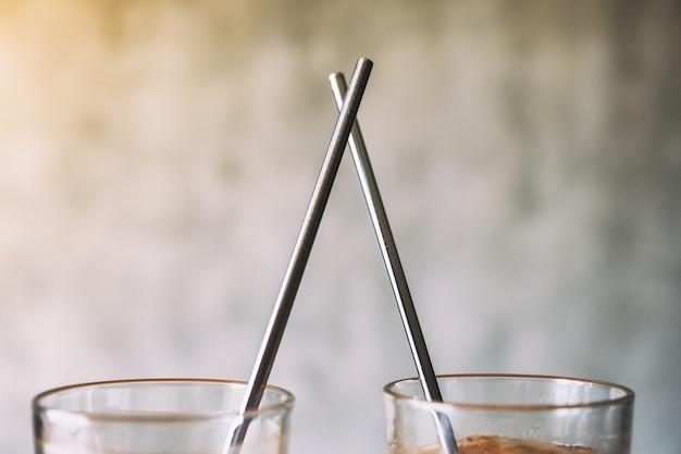 Imagem de close de dois copos de café gelado com canudo de aço inoxidável