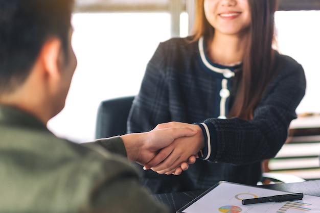 Imagem de close de dois empresários apertando as mãos em uma reunião