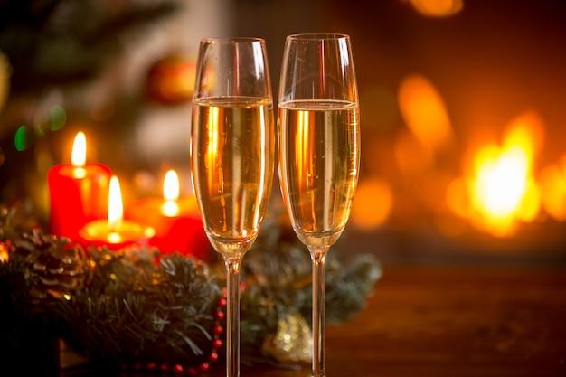 Imagem de close de duas taças de champanhe na frente da guirlanda de natal e da lareira acesa