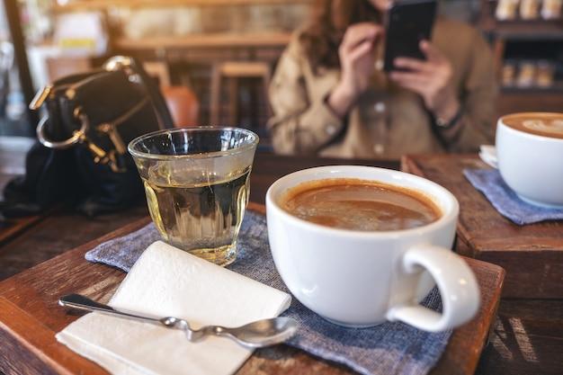Imagem de close de duas xícaras brancas de café quente e um copo de chá na mesa de madeira vintage com uma mulher usando o telefone celular no café