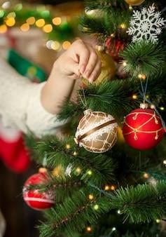 Imagem de close de jovem colocando bugiganga dourada na árvore de natal