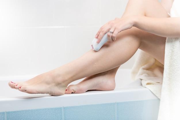 Imagem de close de jovem fazendo depilação no banho