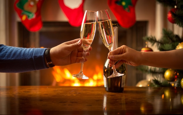 Imagem de close de mãos masculinas e femininas tilintando com taças de champanhe na sala decorada para o natal