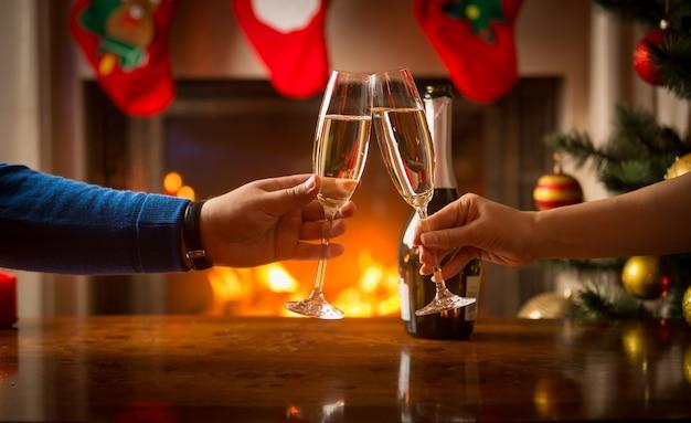 Imagem de close de um homem e uma mulher jantando de natal e tilintando de copos ao lado da lareira a lenha