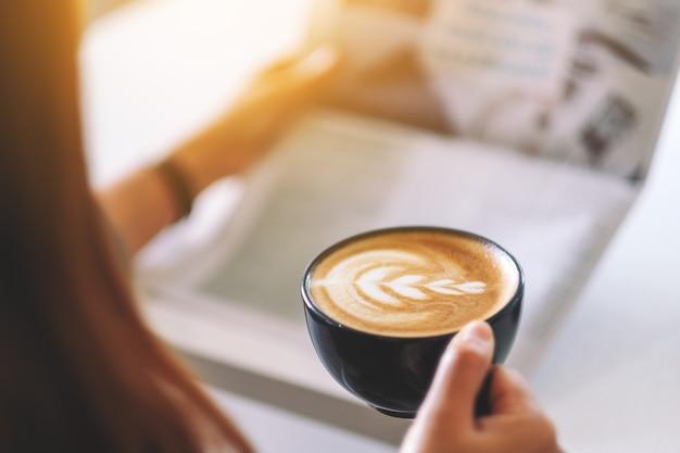 Imagem de close de um homem lendo jornal e tomando café pela manhã