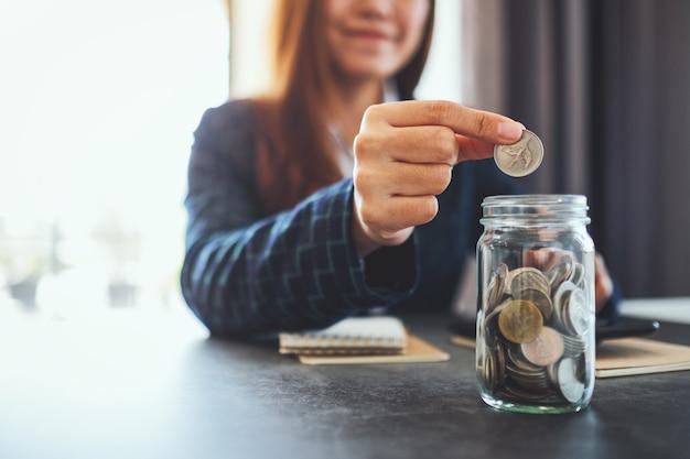 Imagem de close de uma empresária coletando e colocando moedas em uma jarra de vidro