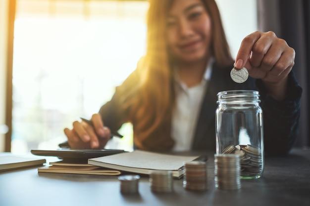 Imagem de close de uma empresária empilhando e colocando moedas em uma jarra de vidro