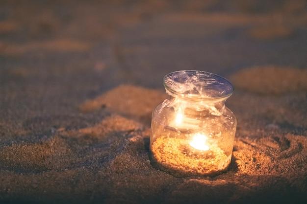 Imagem de close de uma garrafa de vidro porta-velas na praia à noite
