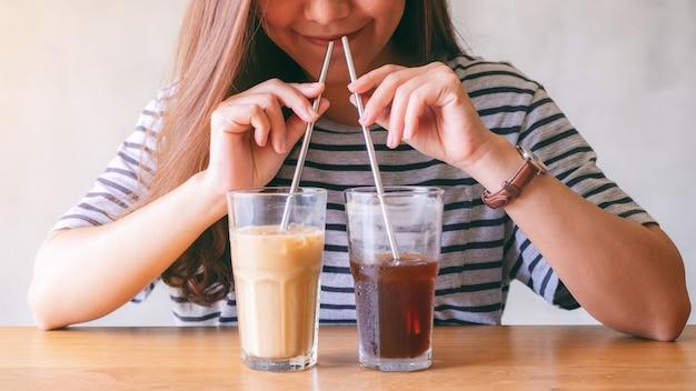 Imagem de close de uma linda mulher asiática bebendo dois copos de café gelado com canudos de aço inoxidável ao mesmo tempo