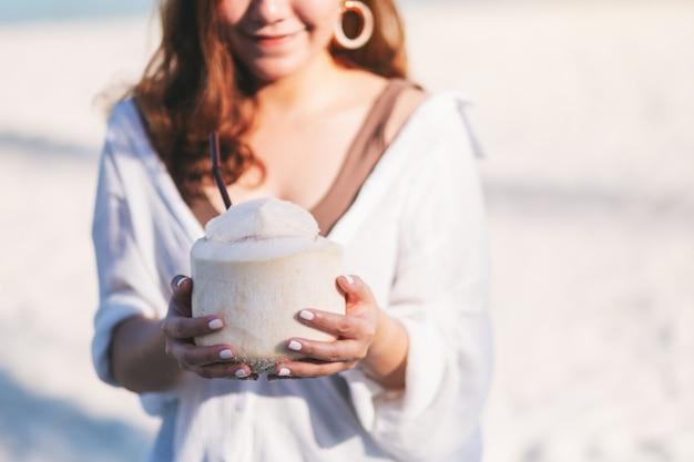 Imagem de close de uma linda mulher asiática segurando e bebendo suco de coco na praia