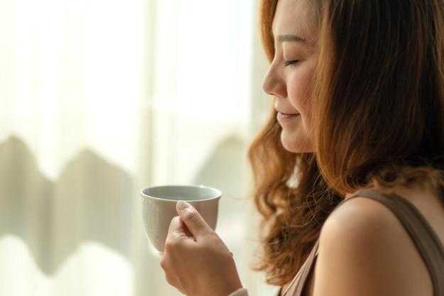Imagem de close de uma linda mulher asiática segurando e cheirando uma xícara de café quente, sentindo-se relaxada pela manhã