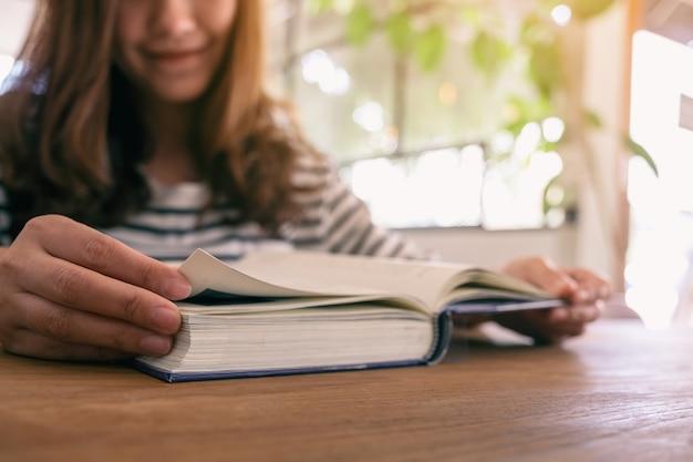 Imagem de close de uma linda mulher asiática segurando e lendo um livro