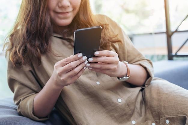 Imagem de close de uma linda mulher asiática segurando, usando e olhando para o telefone inteligente enquanto está sentado na sala de estar