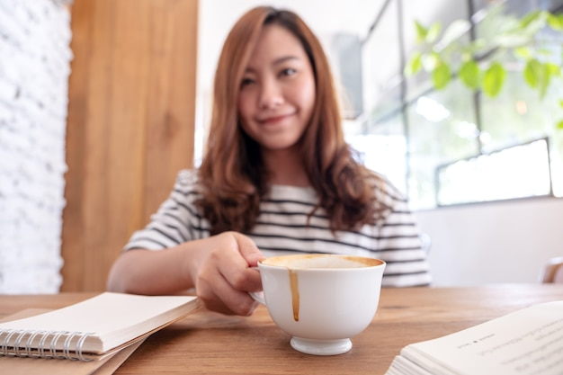 Imagem de close de uma linda mulher asiática tomando café enquanto aprende e lê livros