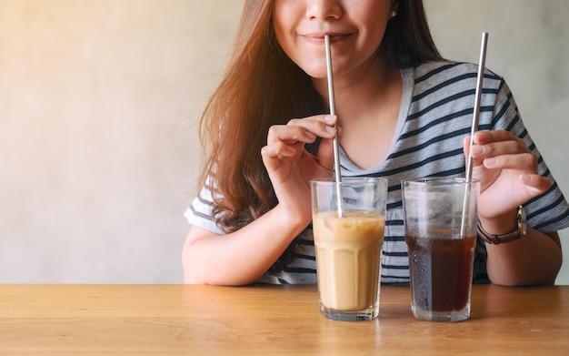 Imagem de close de uma linda mulher asiática tomando café gelado com canudo de aço inoxidável