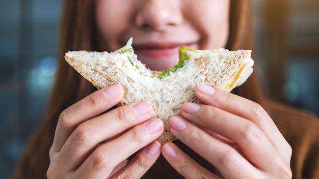 Imagem de close de uma linda mulher segurando e mordendo um pedaço de sanduíche de trigo integral
