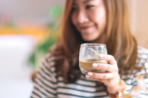 Imagem de close de uma linda mulher segurando um copo de café gelado para beber no café