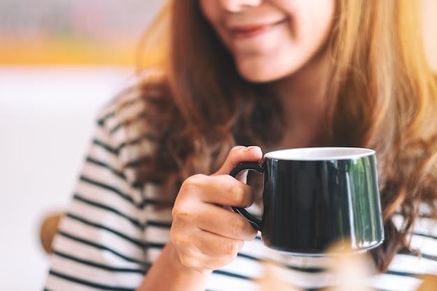 Imagem de close de uma linda mulher segurando uma xícara verde de café quente para beber