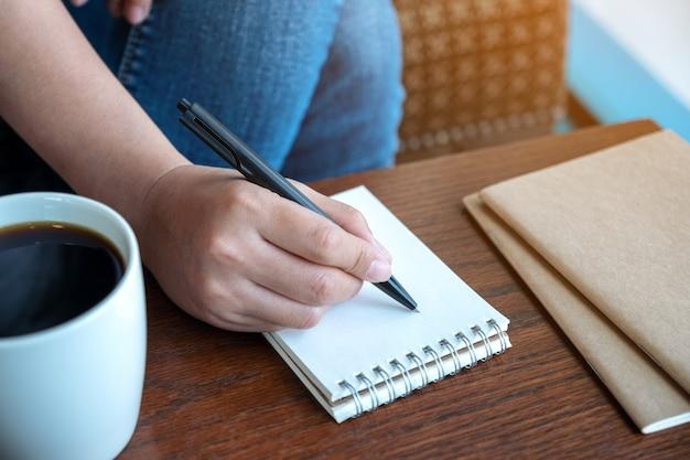 Imagem de close de uma mão de mulher escrevendo em um caderno em branco com uma xícara de café na mesa de madeira