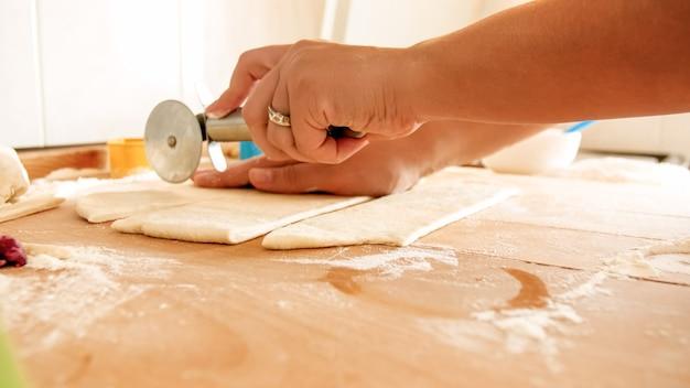 Imagem de close de uma mão feminina segurando uma faca redonda para pizza e cortando massa em uma grande mesa de madeira na cozinha
