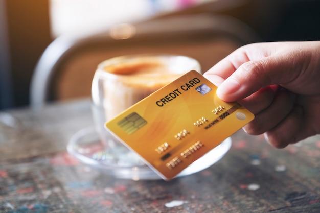 Imagem de close de uma mão segurando e dando um cartão de crédito