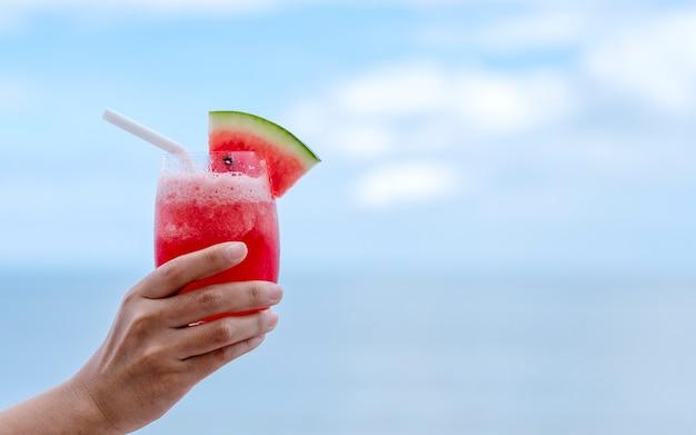 Imagem de close de uma mão segurando um copo de suco de melancia à beira-mar com o fundo do céu azul