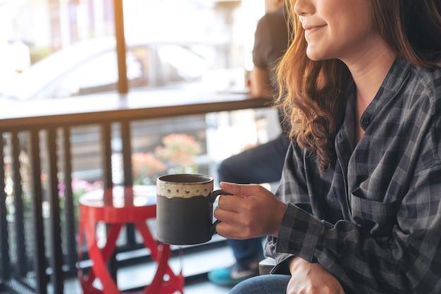 Imagem de close de uma mulher asiática cheirando e bebendo café quente sentindo-se bem no café