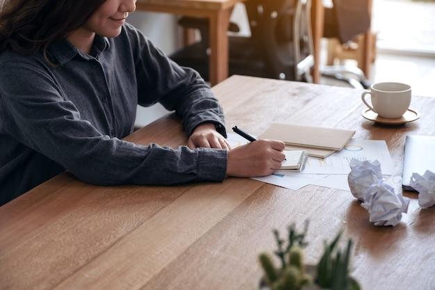Imagem de close de uma mulher de negócios asiática trabalhando e escrevendo em um caderno branco em branco com papéis estragados e laptop na mesa do escritório