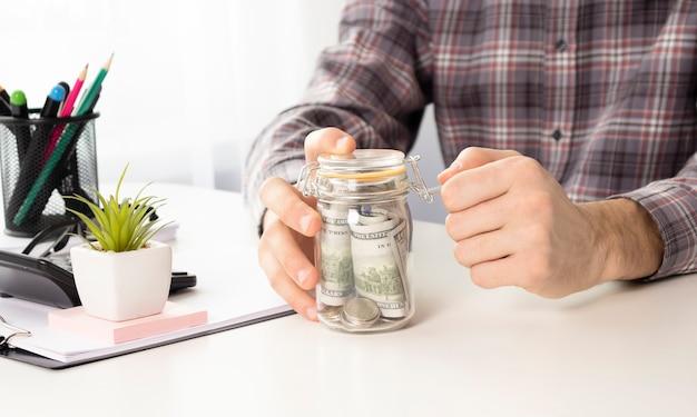 Imagem de close de uma mulher de negócios calculando, empilhando e colocando moedas em uma jarra de vidro para economizar dinheiro e conceito financeiro