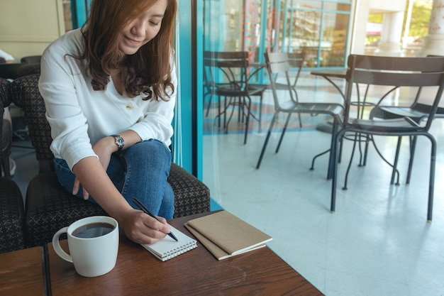 Imagem de close de uma mulher escrevendo em um caderno em branco com uma xícara de café na mesa de madeira