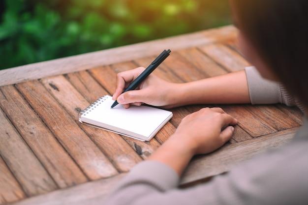 Imagem de close de uma mulher escrevendo em um caderno em branco em uma mesa de madeira ao ar livre