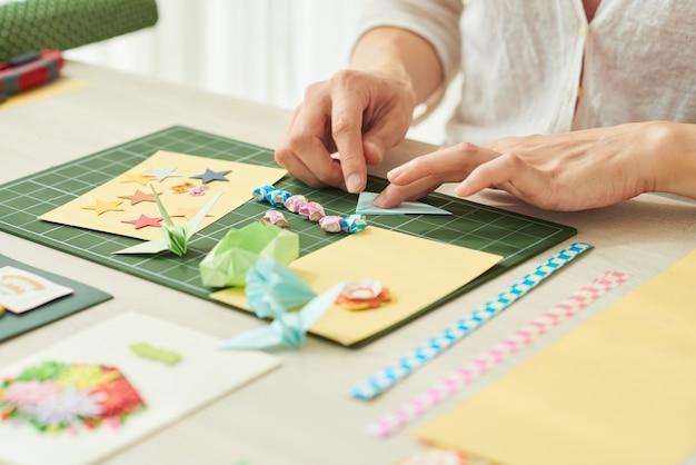 Imagem de close de uma mulher fazendo elementos como estrelas, guindaste ou flores para cartões comemorativos em cores ...