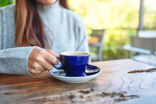 Imagem de close de uma mulher segurando e bebendo café quente ao ar livre