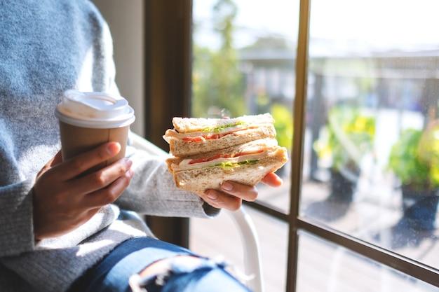 Imagem de close de uma mulher segurando e comendo sanduíche de trigo integral e café pela manhã