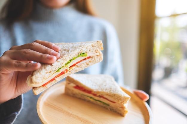 Imagem de close de uma mulher segurando e comendo sanduíche de trigo integral em uma placa de madeira