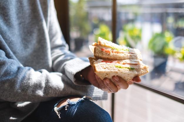 Imagem de close de uma mulher segurando e comendo um sanduíche de trigo integral pela manhã