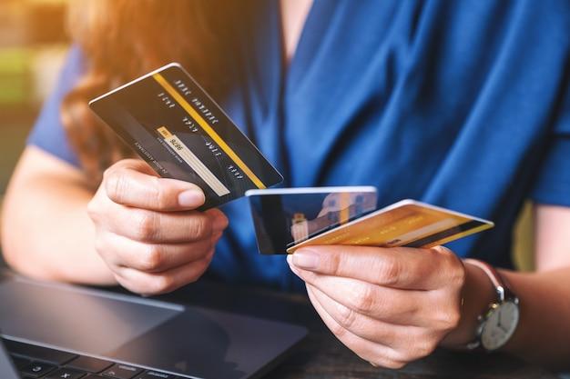 Imagem de close de uma mulher segurando e escolhendo cartões de crédito enquanto usa um laptop