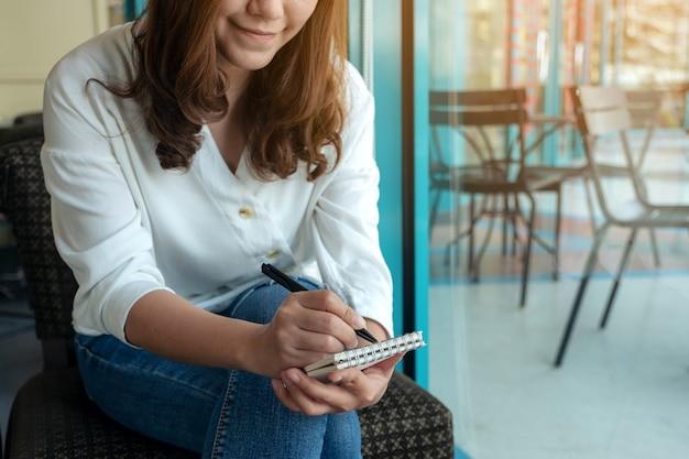 Imagem de close de uma mulher segurando e escrevendo em um caderno em branco