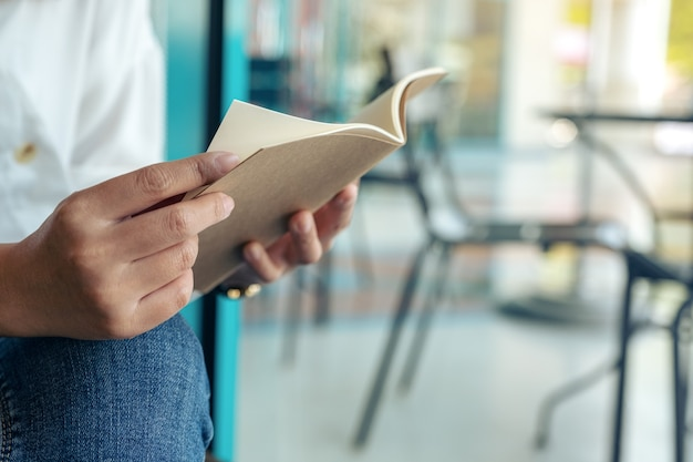 Imagem de close de uma mulher segurando e lendo um livro