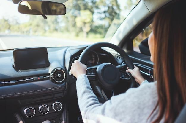 Imagem de close de uma mulher segurando o volante enquanto dirige um carro na estrada
